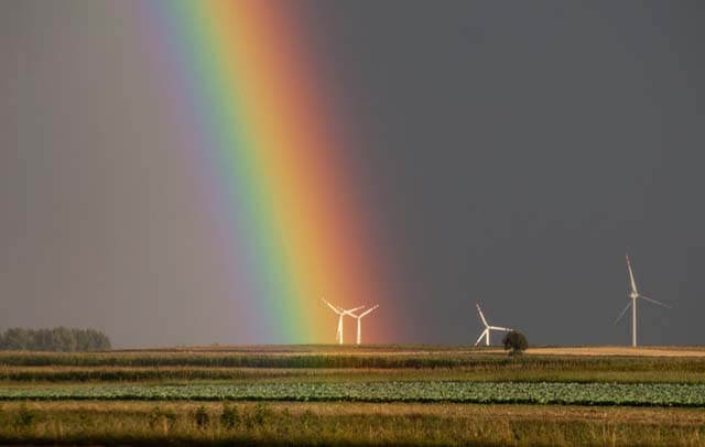 landscape-photography-of-field-with-wind-mill with rainbow